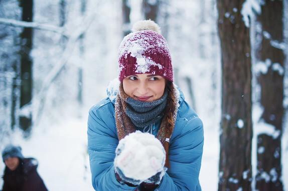 Eine Frau hält einen Schneeball in der Hand und fragt sich ob MLM ein Schneeballsystem ist.